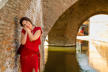 comacchio: environmental portrait of sexy woman in red tight dress smiling while leaning against the walls of an old bridge in the hamlet of an old Italian village, Comacchio, known as Little Venice Stock Photo