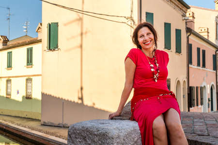 bridge over water: environmental portrait of Mediterranean woman in red dress sitting on ancient bridge over water canals of an old village in Italy, Comacchio, known as Little Venice