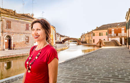 environmental portrait of Mediterranean woman in red dress walking along the water canals of an old village in Italy, Comacchio, known as Little Venice