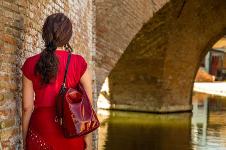 tight dress: environmental portrait of back of woman in red tight dress standing near the walls of an old bridge in the hamlet of an old Italian village, Comacchio, known as Little Venice Stock Photo