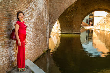 comacchio: environmental portrait of sexy woman in red tight dress standing against the walls of an old bridge in the hamlet of an old Italian village, Comacchio, known as Little Venice