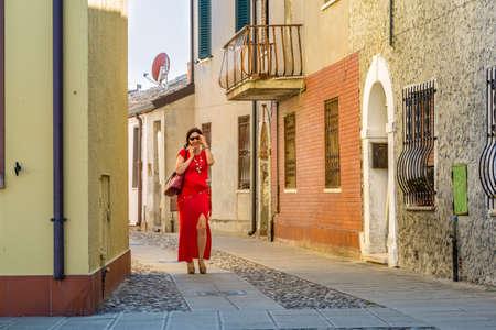 conversaciones: sexy, habla de la señora en el teléfono móvil del tirón mientras se camina en una antigua aldea de la aldea italiana Comacchio, conocida como la pequeña Venecia