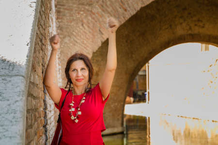 tight dress: environmental portrait of sexy woman in red tight dress smiling and waving fists up while leaning against the walls of an old bridge in the hamlet of an Italian village, Comacchio, known as Little Venice Stock Photo