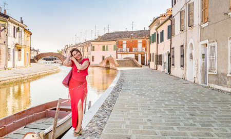 tight dress: environmental portrait of sexy woman in red tight dress walking along the water canals in the hamlet of an old village in Italy, Comacchio, known as Little Venice