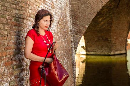 tight dress: environmental portrait of doubtful woman in red tight dress standing against the walls of an old bridge in the hamlet of an old Italian village, Comacchio, known as Little Venice