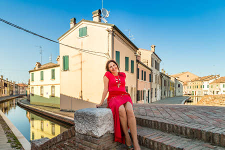 comacchio: environmental portrait of Mediterranean woman in red dress sitting on ancient bridge over water canals of an old village in Italy, Comacchio, known as Little Venice