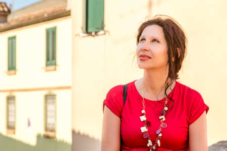 environmental portrait of Mediterranean woman in red dress looking upwards in the hamlet of an old village in Italy