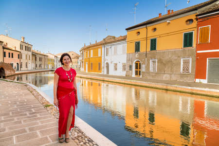 comacchio: environmental portrait of Mediterranean mature woman in red dress walking along the water canals in the hamlet of an old village in Italy, Comacchio, known as Little Venice Stock Photo