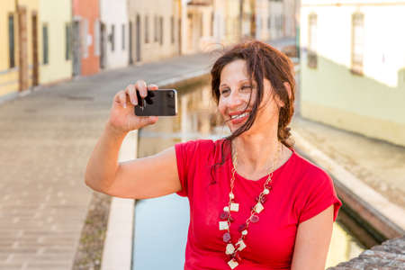bridge over water: environmental portrait of Mediterranean woman in red dress taking a selfie while sitting on ancient bridge over water canals of an old village in Italy, Comacchio, known as Little Venice