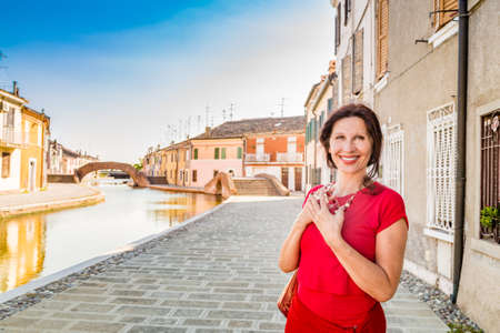 comacchio: environmental portrait of cute Mediterranean woman in red dress walking with hands over chest  along the canals of an old village in Italy, Comacchio, known as Little Venice