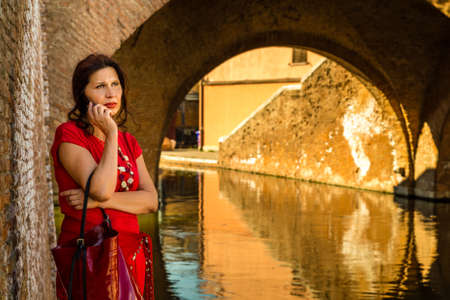 tight dress: environmental portrait of worried woman in red tight dress talking on phone while leaning against the walls of an old bridge in the hamlet of an Italian village, Comacchio, known as Little Venice Stock Photo