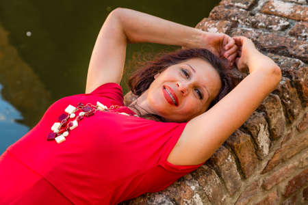 Classy woman with arms over head lying on ancient brick bridge near water canal