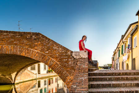 comacchio: Classy woman sitting on ancient bridge amongst historic houses and canals in Comacchio, a village to visit in Italy, also called The Little Venice