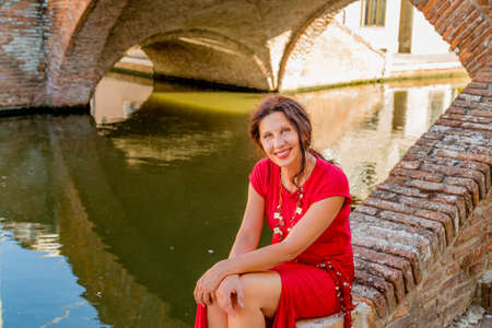Classy mature woman with aging wrinkles sitting on ancient brick bridge in Comacchio, a village also called The Little Venice you must visit in Italy