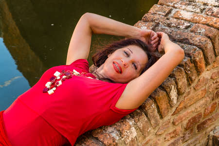 classy: Classy woman with arms over head lying on ancient brick bridge near water canal