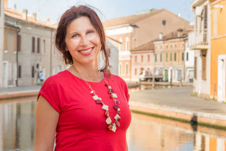 comacchio: Travel tourist woman smiling on vacation amongst historic houses and canals in Comacchio, village to visit in Italy, also called The Little Venice, having fun outdoors during holidays in Europe.