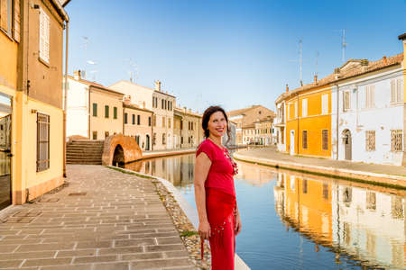 comacchio: environmental portrait of Mediterranean mature woman in red dress walking along the water canals of an old village in Italy, Comacchio, known as Little Venice Stock Photo