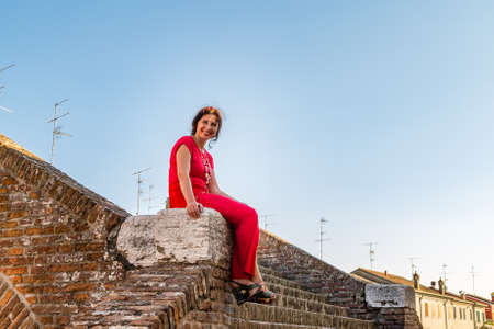 comacchio: Classy woman sitting on ancient bridge in Comacchio, a village to visit in Italy, also called The Little Venice