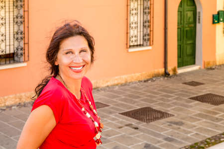 marked: close-up of mature woman with skin marked by wrinkles and age spots in red glass necklace and dress smiling in a paved street of a typical town in Italy