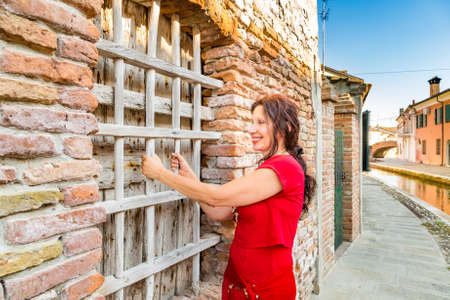 grates: middle-aged woman among colorful historical houses playfully rests on wooden grates of a window in a lagoon town  in Northern Italy