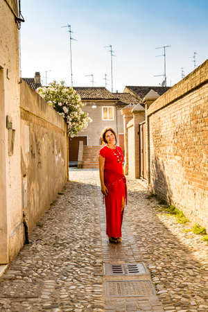 girlish: elegant but genuine elderly woman with girlish eyes smiling walking in the narrow alleys between the brick walls of an ancient medieval village in Italy