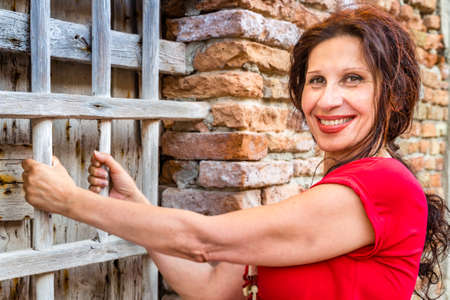 grates: middle-aged woman playfully rests on wooden grates of a window in a town  in Northern Italy