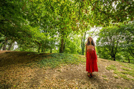 gypsy woman: mature woman dressed in gypsy dress with red skirt and striped T-shirt with boat neck in public park with ground covered by fallen leaves