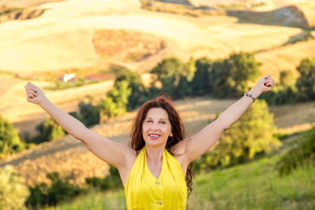 happy and smiling mature woman raises her arms to heaven to rejoice in a hilly countryside landscape