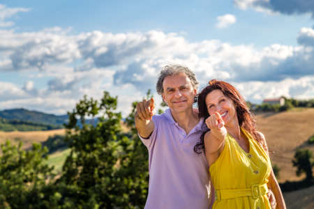 hilly: happy mature couple smiling pointing fingers in the hilly countryside
