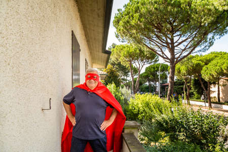 proudly: Funny and smiling senior man posing as superhero with red cape and mask is proudly holding his hands on hips on the balcony of his house