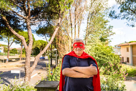 residential neighborhood: Funny and smiling senior man dressed as superhero with red cape and mask is standing with crossed arms on the balcony of his house in a quiet residential neighborhood