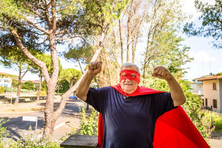 residential neighborhood: Funny and smiling senior man posing as superhero with red cape and mask is showing muscles raising arms in a quiet residential neighborhood Stock Photo
