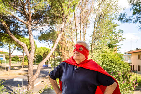 residential neighborhood: Funny and smiling senior man posing as superhero with red cape and mask is standing looking up with fierce and proud frown in a quiet residential neighborhood