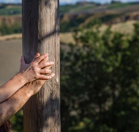 madura mujeres entregar su lado macho descansando en un poste de madera en el fondo de un tranquilo campo, colinas
