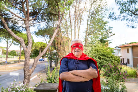 residential neighborhood: Funny and smiling senior man dressed as superhero with red cape and mask is standing with crossed arms in a quiet residential neighborhood Stock Photo