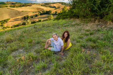 grassy: happy mature couple sitting in a grassy field in countryside