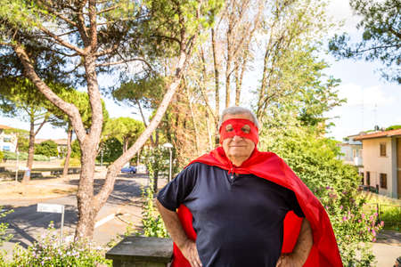 proudly: Funny and smiling senior man posing as superhero with red cape and mask is proudly holding his hands on hips in a quiet residential neighborhood Stock Photo