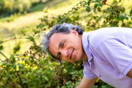 fascinating: fascinating mature man is leaning towards a bush