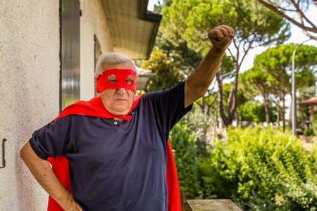 residential neighborhood: Funny and happy senior man posing as superhero with red cape and mask is raising arm preparing to fly in a quiet residential neighborhood Stock Photo