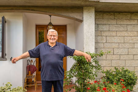 joyfully: happy old man joyfully welcomes you to his house, spreading his arms in the garden Stock Photo