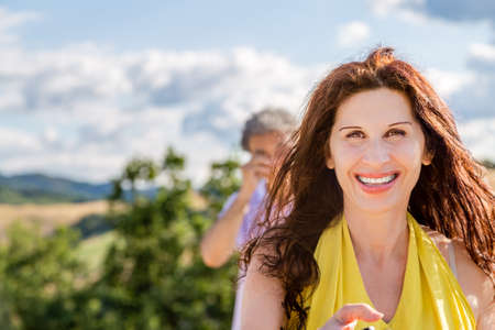 taking a wife: Wife and husband, a mature couple, taking a selfie but while the woman is smiling, the man is rubbing his eyes in the country background Stock Photo