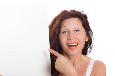 somatic: Happy mature woman with Arab and Middle Eastern somatic traits and long brown hair dyed with henna  smiles pointing her finger at blank white signboard she is holding in portrait orientation Stock Photo
