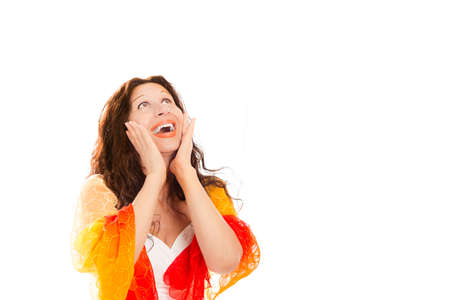 agape: Excited adult Mediterranean woman smiling with open mouth while holding hands on cheeks and looking upwards isolated on white background Stock Photo