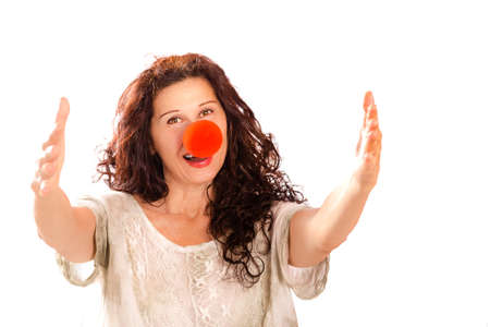 clown nose: Elderly lady with arms outstretched in a welcoming pose is offering an hug while wearing a red clown nose, isolated on white