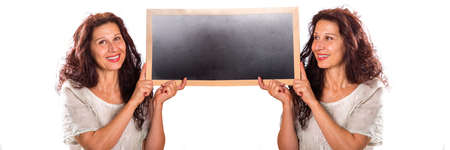 beautiful middle-aged woman with wrinkles and aging skin holding a black chalkboard with a clone of herself in a multiplicity photo isolated on white Foto de archivo