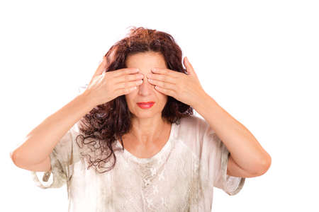 attractive middle aged woman covering her eyes with hands imitating the buddhistic monkey, see no evil, isolated on white Stock Photo