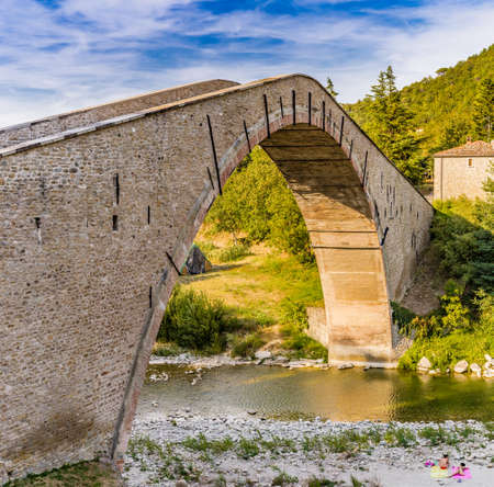 500 years old hog backed Renaissance bridge connecting two banks with single span in Italian Countryside