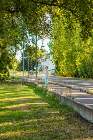 keeping fit: elderly woman in suit keeping fit while enjoying a healthy walk amid the greenery of a city park Stock Photo