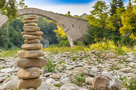 corcovado: pile of stones in front of 500 years old hunchback Renaissance bridge connecting two banks with single span in Italian Countryside Foto de archivo
