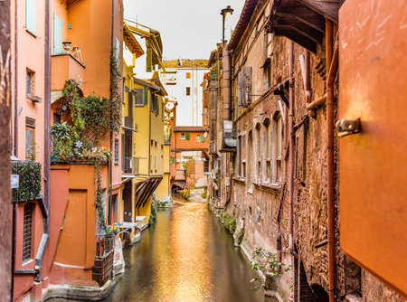 Old water canal hidden behind a window in Bologna downtown in Italy